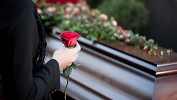 Woman holds rose beside coffin