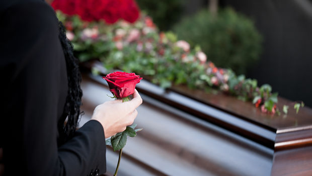Woman holds rose at coffin